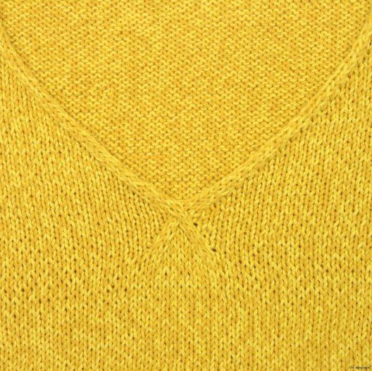 Zoom sur le point du col V du pull femme tricoté au point jersey et côtes.